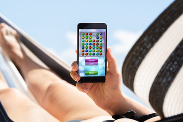 Woman Lying On Hammock Playing Video Game On Mobile Phone