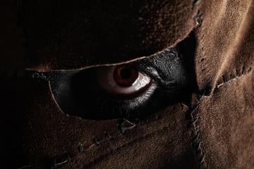 Evil murderer eye in leather mask. Wall mural