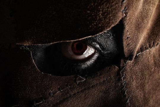 Horror photo of  evil psycho resial murderer eye in leather mask.