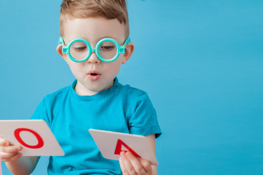 Cute little boy with letter on background. Child learn letters. Alphabet