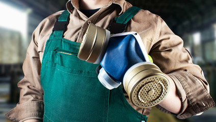 Worker in green overall outfit with respirator.