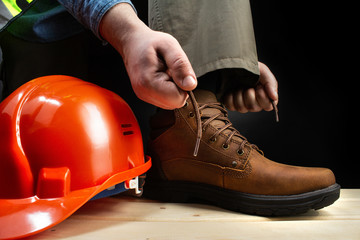 Worker with helmet lacing up leather boots.