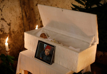 A picture is seen beside casket of the body of 2-1/2-year-old Guatemalan migrant Wilmer Josue Ramirez, during his wake at his home in the village of Olopa