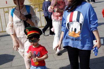 "A boy wears a T-shirt reading ""U.S.A."" and a Chinese military hat in Tiananmen Square in Beijing"