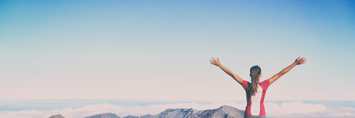 Winning success banner woman reaching summit goal with arms up in the air panorama. Blue sky background. Girl living her life to the fullest fulfilling her dreams - bucket list concept.