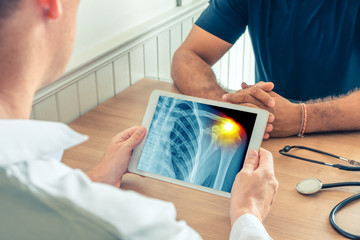 Doctor holding a digital tablet with x-ray of the chest of the patient. Pain on the shoulder