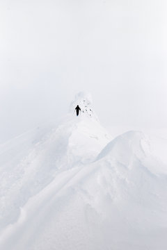skier touring on top of a snowy mountain peak in a whiteout