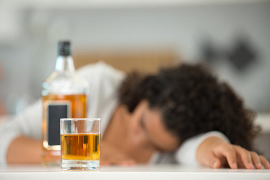 woman slumped over beside a bottle of alcohol