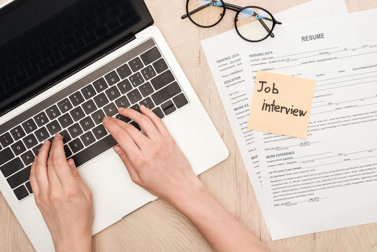 cropped view of recruiter typing on laptop keyboard near glasses, resume templates and sticky note with job interview lettering