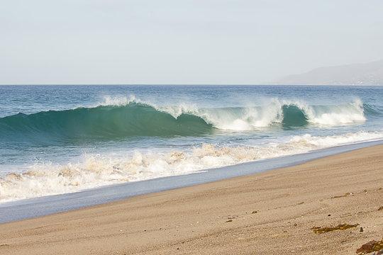 breeaking tube wave with foam creasting toward shoreline with backwash on sandy beach
