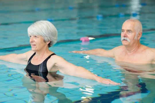 senior happy couple in swimming pool lesson