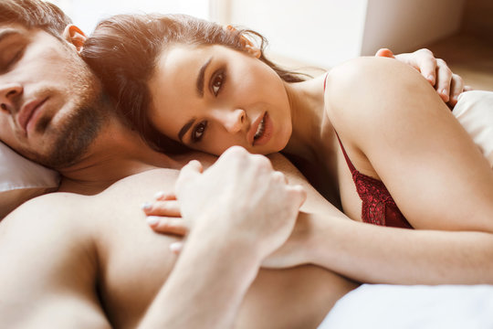 Young sexy couple have intimacy on bed. Cut view of beautiful female brunette looking on camera and smile a bit. He hold her hand in his. Sleeping together. Woman lying on his chest.