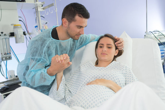 Woman in labor, partner holding her hand