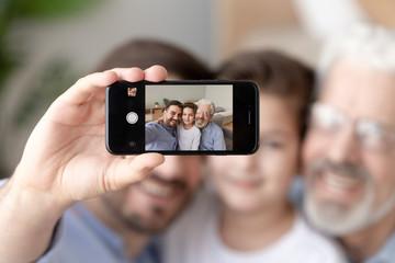 Smiling three generations of men take selfie on smartphone