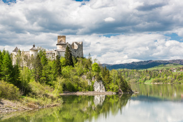 Niedzica castle on cliff at Czorsztyn lake in Poland. Green landscape overview