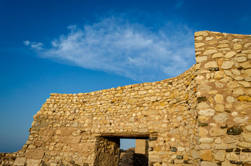 Ruins of a stone wall of an ancient fort with blue sky - Muttrah Fort, Muscat, Oman.
