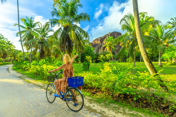 La Digue, Seychelles. Tourist woman on bicycle pointed Giant Union Rock, a monolith at Union Estate a former coconut and vanilla plantation near Anse Source d'Argent. Palm trees grove landscape. Wall mural