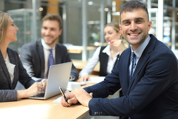 Businessman with colleagues in the background in office.
