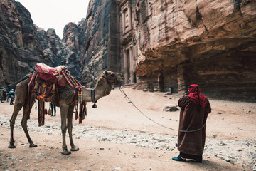 Camel and tourists in front of ancient temple in rock face in Al Khazneh, Petra, Jordan