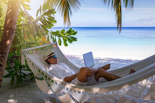Arbeiten im Urlaub: Mann mit Laptop auf Hängematte am tropischen Strand unter Palmen