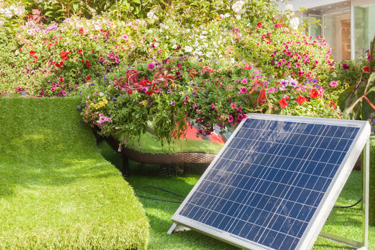 Solar panell in back or front house yard with trees and flowers warm sunny spring or summer day.