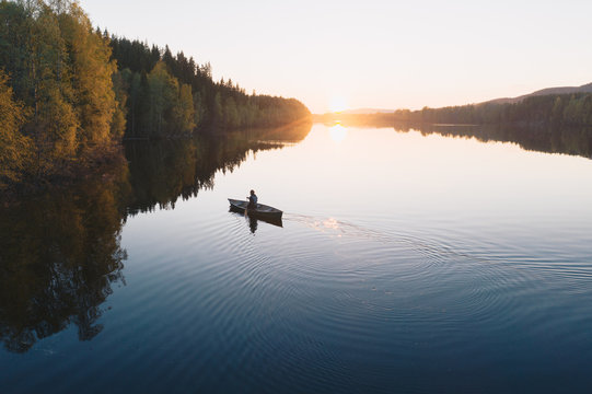 Young man paddling a canoe boat towards horizon at sunset on a reflecting calm river with trees around in Europe