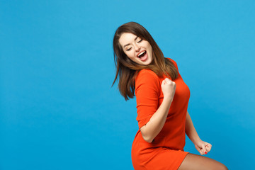 Beautiful excited brunette young woman wearing red orange dress doing winner gesture, say Yes isolated over blue wall background, studio portrait. People lifestyle fashion concept. Mock up copy space.