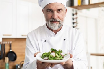 male cook chef decorating garnishing prepared salad dish on the plate in restaurant commercial kitchen.