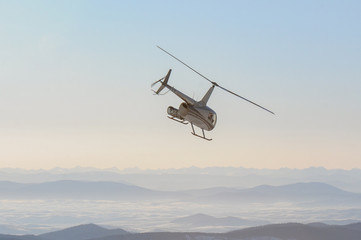 A helicopter flying off to the mountain peaks which are hidden in the fog