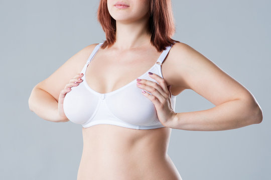 Breast test, woman examining her breasts for cancer, big natural boobs on gray background