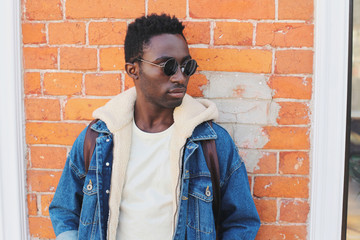 Wall Mural - Fashion close-up portrait african man wearing jeans jacket, black sunglasses on city street over brick wall background