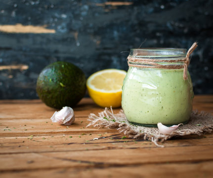 Homemade creamy avocado dressing in a jar on wooden background