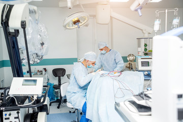 Brain surgery. Group of surgeons in operating room with surgery equipment.