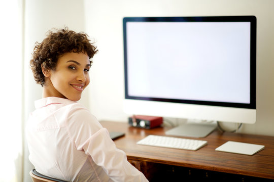 young african american woman sitting by computer screen