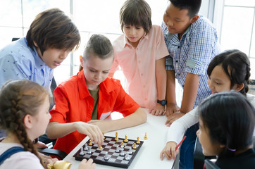 A group of children gathered to play chess in his spare time from studying.