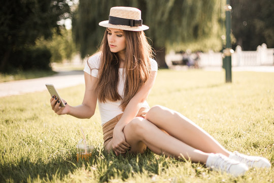 Beautiful young woman sitting on grass and using phone in summer park.