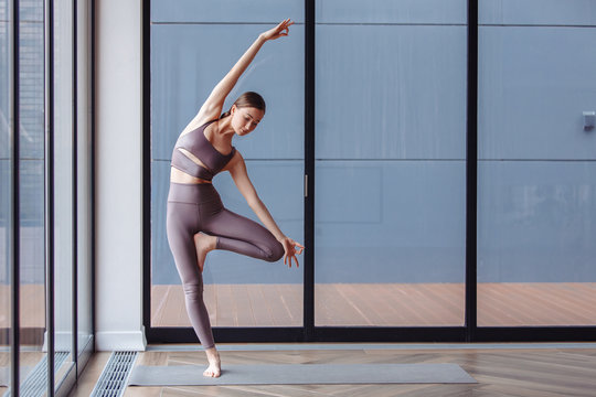 Athletic young girl yoga instructor in purple pants and bra doing vrikshasana standing near the large blue windows of gym. Concepts of flatfoot correction and poor posture. Yogi woman practice asana