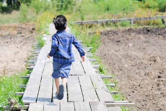 The boy is running forward.