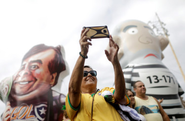 A woman takes a selfie between inflatable dolls, depicting former Brazilian president Luiz Inacio Lula da Silva and Lower House President Rodrigo Maia during a pro-government demonstration in Rio de Janeiro