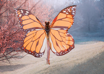 A monarch butterfly enjoys flying. A young woman with a perfect body, long legs flies up into the sky. Huge, painted wings opened like a moth. Art photo from the back, without a face. Sun rays