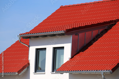 Dormer with stainless steel cladding on a new roof with red