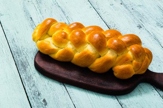 fresh challah bread on cutting board, blue wooden table