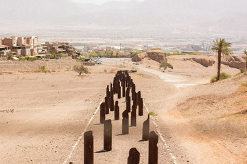 abandoned industrial wasteland concept picture in Middle East poor third world country with rust iron stick from ground in desert and Jewish city background, unfocused metal fence string foreground