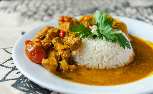 Curry chicken bright juicy with white rice on plate over the tablecloth background. side view.