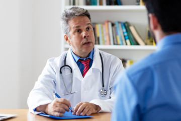 Mature doctor explaining therapy to patient