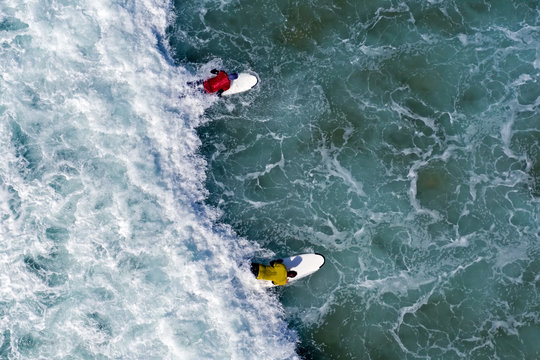 Aerial shot from surfers trying to catch a wave in the ocean
