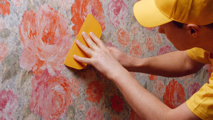 Builder making home renovation. Close up decorator hanging wallpaper on the wall. Repair sevice concept.