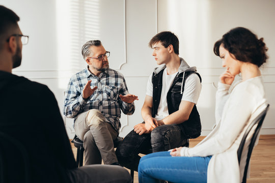 Psychologist talking about twelve-step program to addicted man during group support meeting