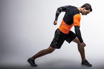 Muscle male model in trend sportswear posing on gray background. Studio shoot.