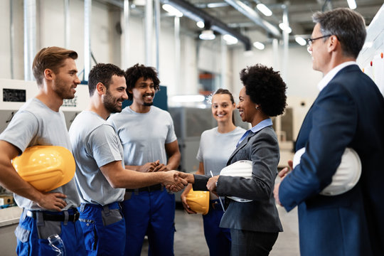 Happy African American businesswoman shaking hands with one of factory workers.